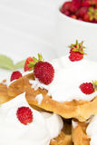 Waffles with wild strawberries and whipped cream on white table Royalty Free Stock Photo