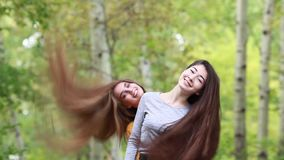 Wag head girls with long thick hair. Hair care. Two beautiful young happy girl friends flap their long plush thick hair in the park summer day stock video footage