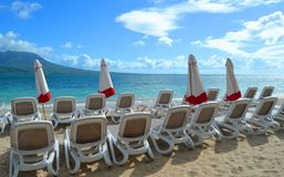 Wagen-Aufenthaltsräume und Regenschirme auf dem Strand Lizenzfreies Stockfoto