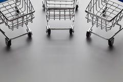 Wagen mit drei Selbstbedienungseinkaufslaufkatzen auf grauem Hintergrund lizenzfreie stockbilder