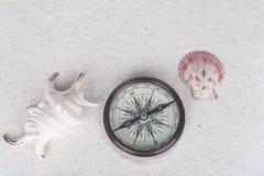 Wagen Sie Dekoration mit Kompass, Oberteil und Tritonshorn auf dem weißen Sand Lizenzfreie Stockfotos