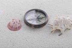 Wagen Sie Dekoration mit Kompass, Oberteil und Tritonshorn auf dem weißen Sand Stockfotografie