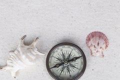 Wagen Sie Dekoration mit Kompass, Oberteil und Tritonshorn auf dem weißen Sand Stockbild