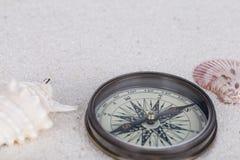 Wagen Sie Dekoration mit Kompass, Oberteil und Tritonshorn auf dem weißen Sand Lizenzfreies Stockbild