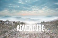 Wagen Sie gegen den steinigen Weg, der zu nebelhaften Gebirgszug führt Stockfotografie