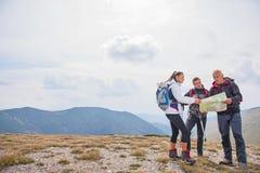 Wagen Sie, reisen Sie, Tourismus, Wanderung und Leutekonzept - Gruppe lächelnde Freunde mit Rucksäcken und Karte draußen lizenzfreies stockbild