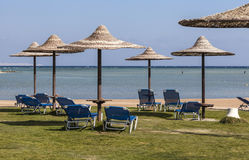 Wagenaufenthaltsraum und -regenschirm auf dem Strand gegen den blauen Himmel und Lizenzfreie Stockfotos