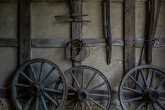 Wagenräder an der alten Lehmziegelmauer des Gutshauses Lizenzfreie Stockfotografie