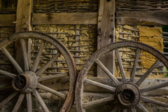 Wagenräder an der alten Lehmziegelmauer des Gutshauses Lizenzfreies Stockfoto