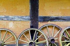 Wagenräder an der alten Lehmziegelmauer des Hauses lizenzfreie stockfotos