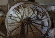 Wagenräder an der alten Lehmziegelmauer des Hauses Lizenzfreies Stockbild