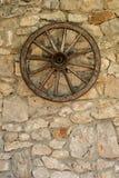 Wagenrad, das an der alten rustikalen Steinwand des Bauernhauses hängt lizenzfreies stockbild