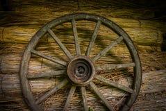 Wagenrad an der alten sraw Wand eines Hauses lizenzfreies stockfoto