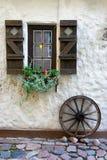 Wagenrad am Fenster mit Fensterläden lizenzfreie stockfotos