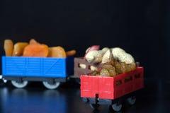 Wagens met van rozijnen, droge abrikozen en pindabonen Stuk speelgoed vrachtwagens Kleine diepte van gebied royalty-vrije stock afbeeldingen