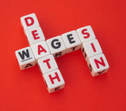 Wages of sin is death. Text ' wages ', ' sin ' and ' death ' inscribed on small white cubes in uppercase letters arranged crossword style with common letters ' a Royalty Free Stock Photography