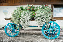 Wagon colored flowered. Colorful wooden wagon with flowers compositions Royalty Free Stock Images