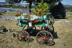 Wagon covered with flowers in the yard in Monastery St. John the Baptist,  Bulgaria Royalty Free Stock Photos