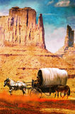 Wagon in the desert on grunge. A western wagon with two horses and a mule, into the desert of Monument Valley, Utah Stock Photo