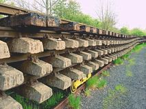 Wagon with extracted old railways. Concrete and wooden sleepers with rail rods Stock Image
