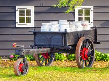 Wagon full of milk cans in a farm yard in Holland. Old grey wagon full of metal milk cans in a farm yard in Holland Stock Image