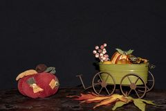 wagon with harvest an,d fruits Harvest and a giant red cloth pumpkin royalty free stock photo