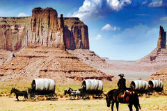Wagon train. A wagon train crossing the desert of Monument Valley under the attentive  surveillance of one of its drivers Royalty Free Stock Images