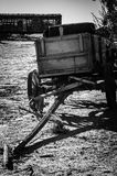 Wagon and Train. A black and white photo of an old wagon with an old slatted train car in the background Royalty Free Stock Images