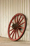 Wagon wheel. Red antique wagon wheel leaning against a steel shed Royalty Free Stock Photo