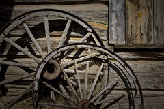 Wagon Wheel. Two wagon wheels against a cabin background stock photos