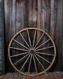 Wagon Wheel. Leaning on barn wall stock photo