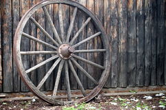 Wagon Wheel. Antique wagon wheel with metal rim against wooden wall Stock Image