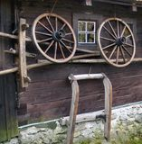 Wagon wheel on old log house. Wagon wheels on side of old log house with rural farm equipment in foreground, Cicmany village, Slovakia royalty free stock images