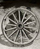 Wagon wheel. Old wooden wagon wheel against wall stock image