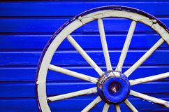 Wagon Wheel by Painted Blue Wall Stock Photography