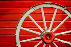 Wagon Wheel by Painted Red Wall Royalty Free Stock Photo