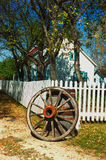 Wagon Wheel and Picket Fence. Old fashioned country home with white picket fence and wagon wheel Stock Photo