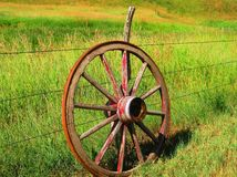 Wagon wheel. A picture a wagon wheel leaning on a fence post royalty free stock image