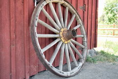 Wagon Wheel. An old wagon wheel rests on the side of a red barn Royalty Free Stock Photo