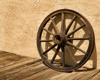 Wagon Wheel Wheel Against a Stucco Wall in Arizona. An old wagon wheel, an iconic symbol of the American West, sits on a wooden sidewalk and leans against a stock image