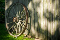 Wagon Wheel. Wooden wagon wheel resting on a weathered mossy barn Stock Photo