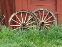 Wagon Wheels. A pair of old wagon wheels from days gone by lean against a building in the west Stock Image