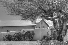 Wagon Wheels along Wall in Southwestern Town. Wagon wheels are resting along a wall in a southwestern area under a tree in the daytime Stock Photography