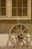 Wagon whell by barn. Old wagon whell propped up on barn wall Stock Photography