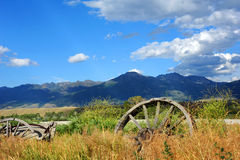 Wagons face Absaroka Mountain Range. Abandoned and broken down wagons face the Absaroka Mountain Range in Paradise Valley, Montana.  Tall grass and weeds have Royalty Free Stock Images