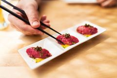 Wagyu beef tartar with yuzu sauce. Cured yolk and caviar- man hand taking a piece with chopsticks Stock Photos