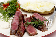 Wagyu ribeye dinner closeup. Closeup on slices of grilled gourmet wagyu rib-eye steak served with horseradish sauce, a baked potato and a fresh green salad Royalty Free Stock Photo