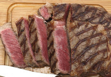 Wagyu steak cut on board. High angle view of a partly-sliced grilled wagyu beef ribeye steak viewed from above Stock Photo