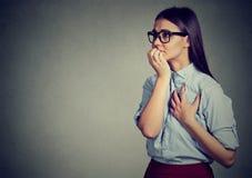 Wahająca kobieta gryźć jej paznokcie pragnie dla coś lub niespokojnych Obrazy Stock