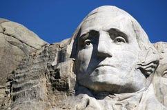 Wahington, Mt 在观看四总统雕刻以后面孔在,它是令人吃惊突然产生坐反对声势浩大,巨型的岩石的人造形状的这个场面 免版税库存图片